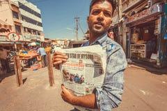 Homme vendant l'étoile de journal de Mysore sur la rue colorée avec des stalles et des magasins du marché Images libres de droits