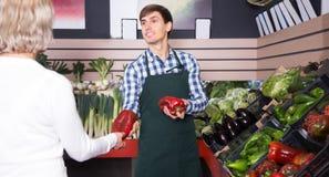 Homme vendant les légumes frais et les herbes photos stock