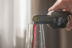 Homme versant le vin rouge de la bouteille Photos libres de droits