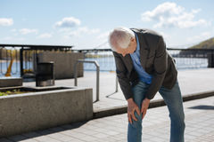 Homme vieillissant ayant la douleur dans son genou sur la promenade Photo stock