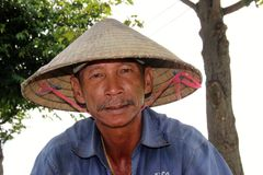 Homme vietnamien dans le chapeau conique traditionnel Photographie stock