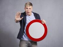 Homme vigilant affichant l'indicateur interdit universel. Photographie stock