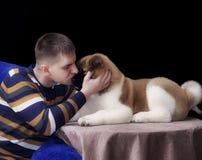 Homme viril blanc embrassant la race Akita de chiot photos stock