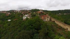 Hommel die boven oude Sighnaghi-stad in Georgië, mening vliegen van steenmuur en huizen stock footage