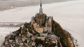 Hommel die hoog rond beroemd Mont Saint Michel, de oud getijdevesting van de eilandstad en reisoriëntatiepunt vliegen op mistige  stock footage