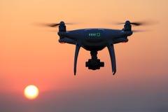 Hommel die met afstandsbediening in lucht en zonsonderganghemel vliegen Royalty-vrije Stock Afbeeldingen