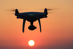 Hommel die met afstandsbediening in lucht en zonsonderganghemel vliegen Stock Afbeelding