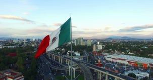 Hommel-luchtmening van het reusachtige Mexicaanse vlag golven In achter, panoramische viw van Mexico-City Vele auto'sdoorgang voo stock footage