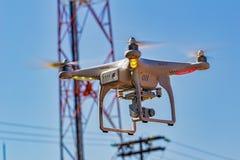 Hommel met camera die met antenne, pool, elektriciteitsdraden en blauwe hemel op de achtergrond vliegen royalty-vrije stock afbeelding