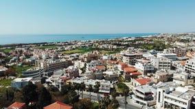 Hommel over de stadspaphos van Cyprus vliegen met gebouwendaken en oceaanoverzees die op achtergrond Luchtschot stock video