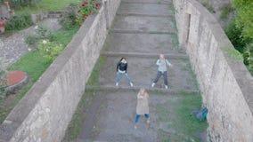 Hommel schieten van drie vrienden die pretdans in oude Italiaanse stad doen stock footage
