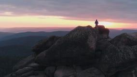 Hommel van de eenzame mens wordt geschoten die zich bovenop een berg bevinden en van de zonsondergang genieten die stock videobeelden