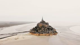 Hommel vliegen links hoog boven iconische Mont Saint Michel-eiland en abdij, episch beroemd reisoriëntatiepunt in Normandië, Fran stock videobeelden