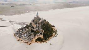 Hommel vliegen links hoog boven Mont Saint Michel, beroemd oriëntatiepunteiland met abdij tijdens eb in Normandië Frankrijk stock videobeelden
