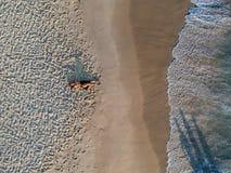 Hommelfoto van vrouw het liggen op het strand tijdens zonsondergang Royalty-vrije Stock Afbeelding
