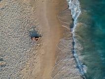 Hommelfoto van vrouw het liggen op het strand tijdens zonsondergang Royalty-vrije Stock Fotografie