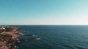 Hommelmening van blauwe overzees met kleine verlaten boot op horizon Stormachtige overzeese golven die rotsachtig strand raken di stock videobeelden