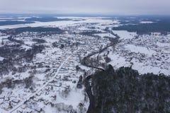 Hommelmening van de winter bos, buigende rivier en klein dorp royalty-vrije stock afbeeldingen