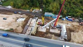 Hommelmening van het gebied van de brugbouw met reusachtige concrete beems en kranen stock footage