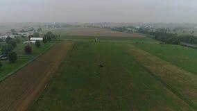 Hommelsatellietbeeld van Amish-Landbouwgronden en Amish-Landbouwer Harvesting in Mist stock videobeelden