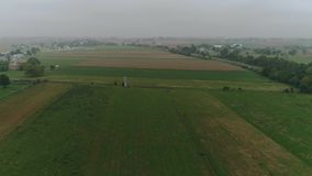 Hommelsatellietbeeld van Amish-Landbouwgronden en Amish-Landbouwer Harvesting in Mist stock video