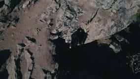 Hommelschot van Silhouet van paar het kussen aan het eind van grote rots stock footage