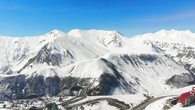 Hommelvliegen over de Gudauri-bergen in Georgië Zonnig weer in de wintertijd Weergeven van de skilift stock footage