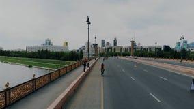 Hommelvliegen over een brede weg met fietsers Zij zijn spelen een rol in de wedstrijd van het wereldtriatlon met het cirkelen, lo stock video