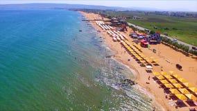 Hommelvlucht over het zandstrand van de Krim met paraplu's stock videobeelden