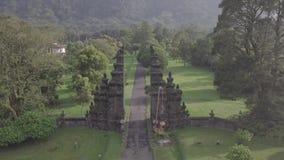 Hommelvlucht over overweldigende mening van steenpoorten en berg op Bali, Indonesië stock videobeelden