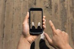 Hommes à l'aide du téléphone intelligent prenant la photo de ses pieds Photographie stock libre de droits