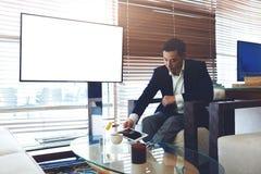 Hommes élégants se préparant au briefing utilisant le pavé tactile Image stock