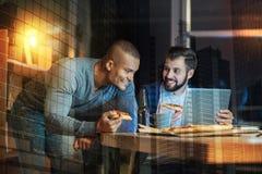 Hommes émotifs regardant l'un l'autre tout en mangeant la pizza et le sourire Image stock