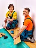 Hommes étendant le parquet à la maison Image stock