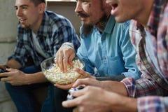 Hommes adultes enthousiastes jouant des jeux vidéo Images stock