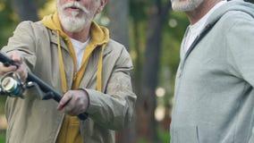 Hommes adultes essayant la canne à pêche avec le nouvel équipement professionnel, passe-temps récréationnel clips vidéos