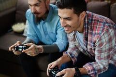 Hommes adultes modernes jouant des jeux vidéo Photos stock
