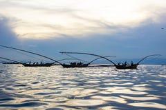 Hommes africains est pêchant sur un lac avec la réflexion du sun sur l'eau image libre de droits