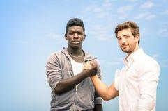 Hommes afro-américains et caucasiens se serrant la main Photographie stock libre de droits