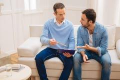 Hommes agréables énergiques discutant leurs affaires photos stock