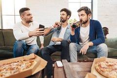 Hommes agréables beaux prenant une petite gorgée de bière Image libre de droits