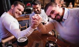 Hommes agréables gais armwrestling dans le bar Photo stock