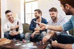 Hommes agréables gais jouant le jeu de poker Image libre de droits