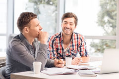 Hommes agréables s'asseyant à la table Image stock