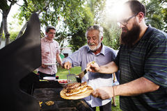 Hommes aidant faisant cuire le bifteck fait maison à la partie d'été de bakcyard Image libre de droits