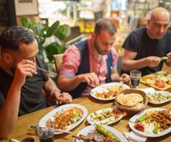 Hommes arabes dans le restaurant appréciant la nourriture du Moyen-Orient Photo libre de droits