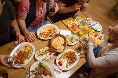 Hommes arabes dans le restaurant appréciant la nourriture du Moyen-Orient Images stock