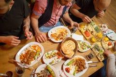 Hommes arabes dans le restaurant appréciant la nourriture du Moyen-Orient Photos libres de droits