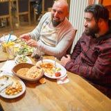 Hommes arabes dans le restaurant appréciant la nourriture du Moyen-Orient Image stock