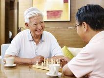 Hommes asiatiques supérieurs jouant des échecs Image libre de droits